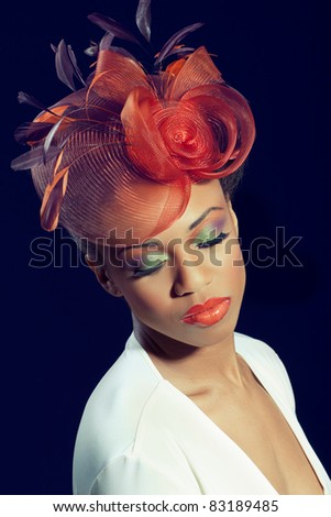 Beautiful young woman with colorful makeup wearing a stylish hat, isolated on black - stock photo