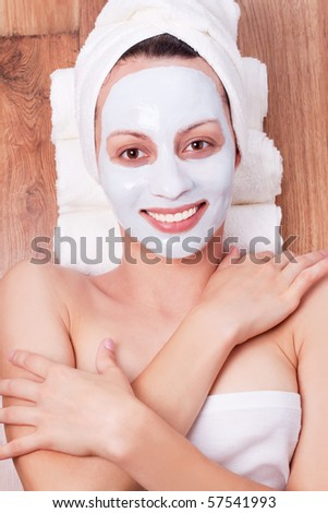 beautiful young woman with cosmetic mask on her face