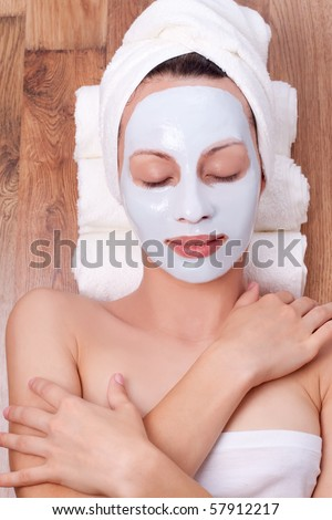 beautiful young woman with cosmetic mask on her face - stock photo