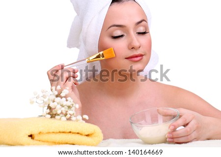 Beautiful young woman with cream for face mask and towel on her head isolated on white - stock photo