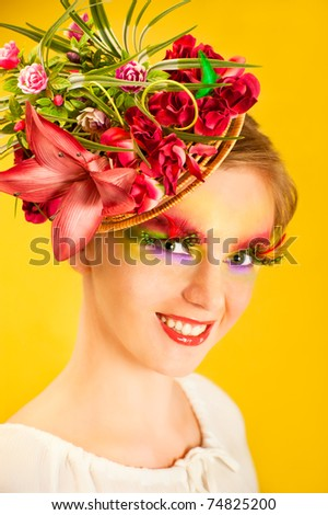 Beautiful young woman with creative flower cap. Artistic makeup with long feather artificial eyelashes and bright colorful eyeshadow