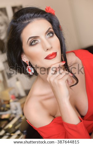 Beautiful young woman with creative make-up and hair style posing. Fashionable attractive brunette with Spanish look, indoors shot. Portrait of lady in red with flower in hair and gorgeous eyes - stock photo