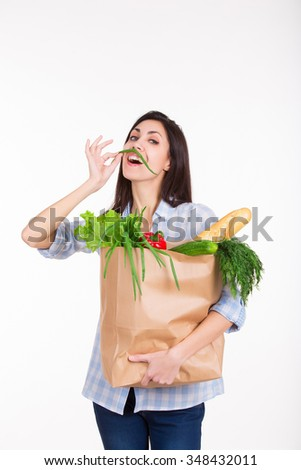 Beautiful young woman with credit card holding paper bag with groceries from grocery shop