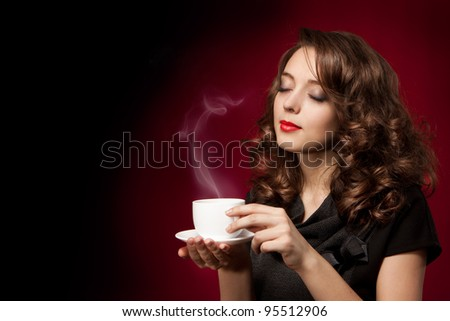 Beautiful young woman with cup of tea - stock photo