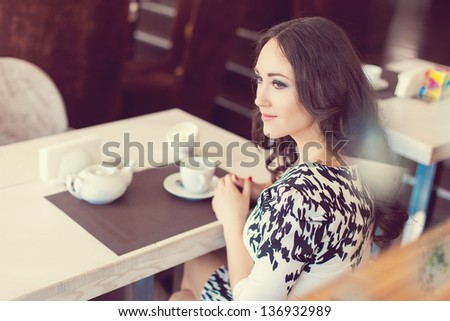 Beautiful young woman with cup of tea at cafe - stock photo