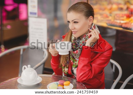 Beautiful young woman with cup sitting in cafe.  Cookies macarons dessert. Beautiful Girl Drinking Tea sitting in front of the window outdoor. Woman with the Cup of Hot Beverage. - stock photo