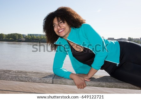 beautiful young woman with curly hair playing sports in the city