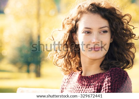 Beautiful young woman with curly hair posing outdoors at autumn - stock photo