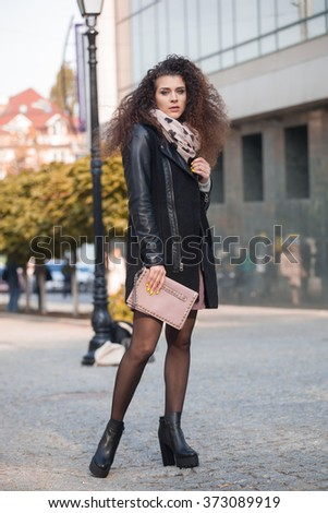 Beautiful young woman with curly hair walking in the city. Autumn photo