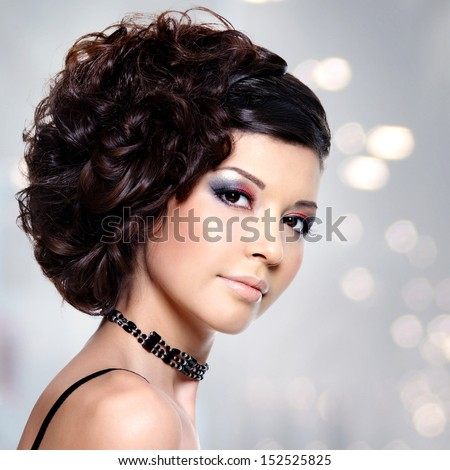 Beautiful young woman with curly hairstyle and bright makeup