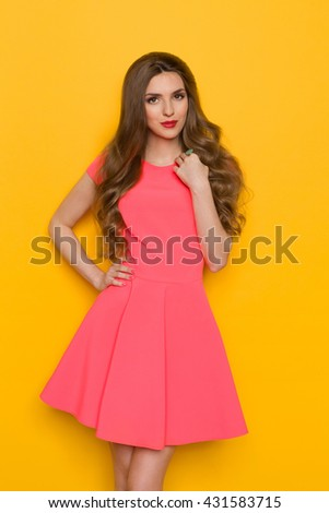 Beautiful young woman with curly long brown hair in pink mini dress posing with hand on hip and looking at camera. Three quarter length studio shot on yellow background. - stock photo