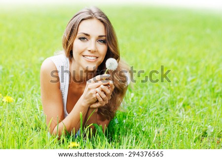 beautiful young woman with dandelion lying on grass - stock photo