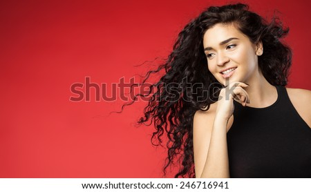 Beautiful young woman with dark flowing curly hair and perfect skin on a red background - stock photo