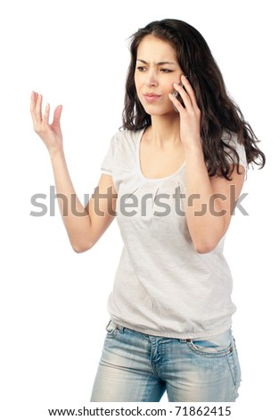 beautiful young woman with dark wavy hair looks frustrated while talking on the phone. Isolated on white background. - stock photo