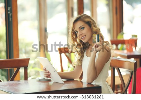 Beautiful young woman with digital tablet and credit card in cafe
