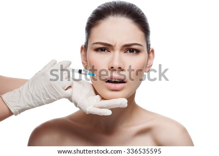 Beautiful young woman with expression of pain on face gets injection in lips from sergeant. Isolated over white background. - stock photo