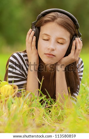 Beautiful young woman with eyes closed, lie on grass and listening to music through headphones, against green of summer park. - stock photo