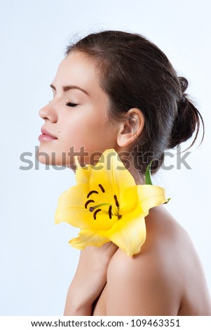 Beautiful young woman with eyes closed. Spa portrait with Lily - stock photo