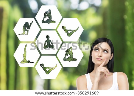 Beautiful young woman with eyes raised up hand to the chin dreaming about taking up sport exercise, yoga, illustrations of several exercises near her, green background, concept of healthy life - stock photo