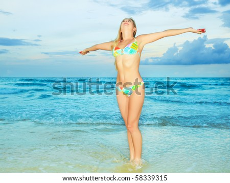 Beautiful young woman with flower at the beach - stock photo