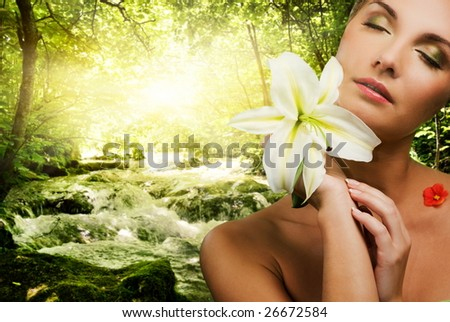 Beautiful young woman with flower in forest - stock photo