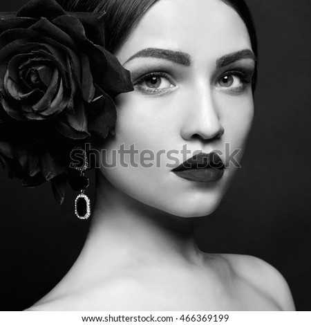 beautiful young woman with flower in hair. beauty girl in jewelry and make-up over black background.close-up monochrome fashion portrait