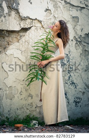Beautiful young woman with flower on background of old wall - stock photo