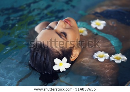 Beautiful young woman with flowers at swimming pool - stock photo