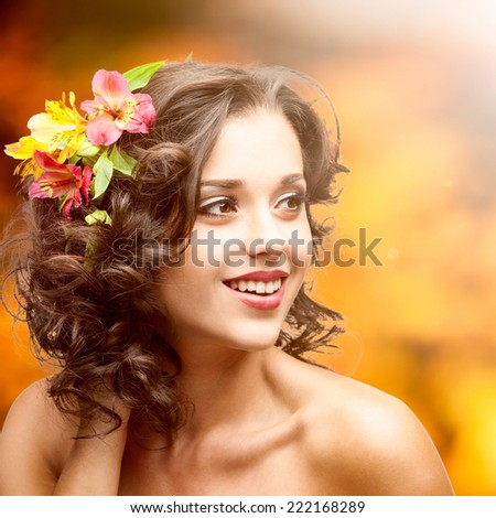 beautiful young woman with flowers in hair over autumn background - stock photo
