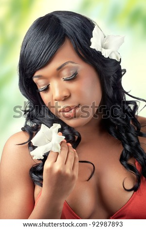 Beautiful young woman with flowers in her hair and hands on beach