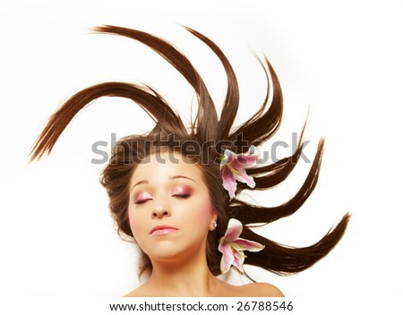 Beautiful young woman with flowers in her hair, eyes closed