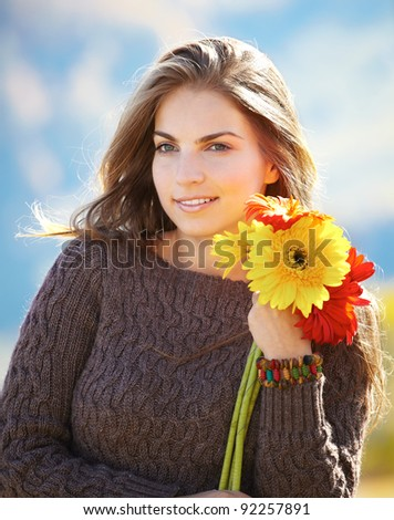 Beautiful young woman with flowers spending a beautiful day outdoors. - stock photo