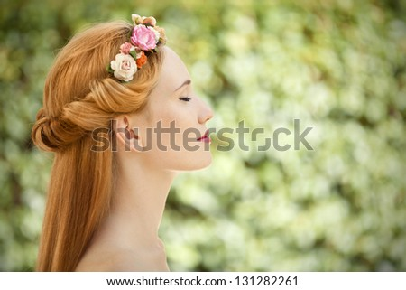Beautiful young woman with flowers wreath in hair on natural green background - stock photo