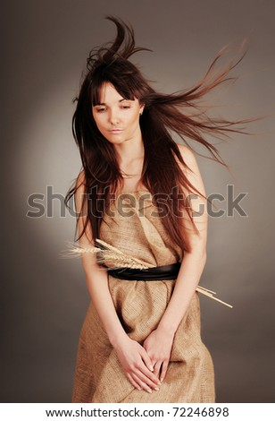 Beautiful young woman with fluttering hair and wheat ears. - stock photo