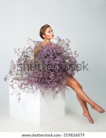 Beautiful young woman with fresh clean skin sitting under large bouquet of flowers over white background. - stock photo