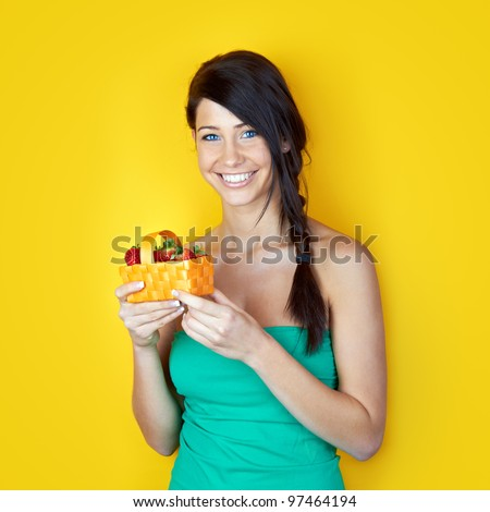 beautiful young woman with fresh red strawberries in a basket against yellow background