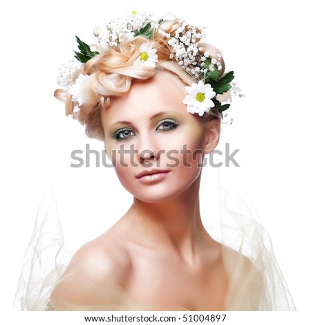 Beautiful young woman with fresh spring flowers in her hair - stock photo