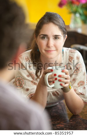 Beautiful young woman with friend holds coffee mug - stock photo