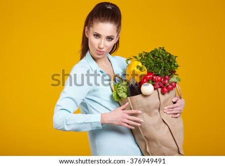 beautiful young woman with fruits and vegetables in shopping bag, isolated on yellow