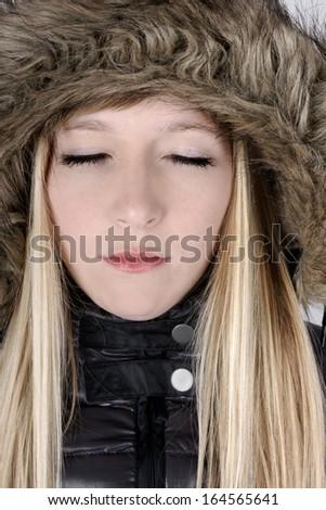 Beautiful young woman with fury hat and closed eyes. - stock photo