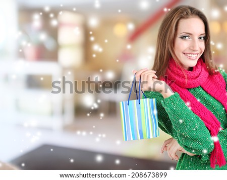 Beautiful young woman with gift bag in shop - stock photo