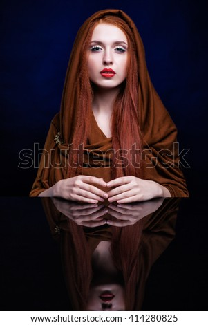 Beautiful young woman with ginger hair and scarf over reflection mirror on blue background