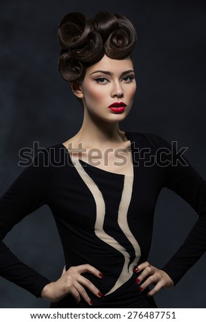 Beautiful young woman with glamorous hairstyle and red lips wearing design shirt - stock photo