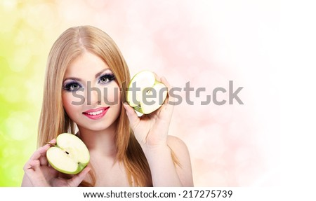 Beautiful young woman with glamour make up and apple on bright background - stock photo
