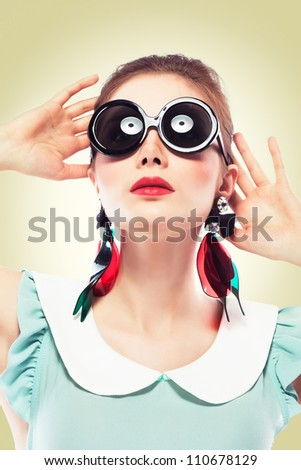Beautiful young woman with glamour red lips make-up wearing round  black plastic-rimmed sunglasses and fancy plastic earrings and looking up on yellow background, pin-up style - stock photo