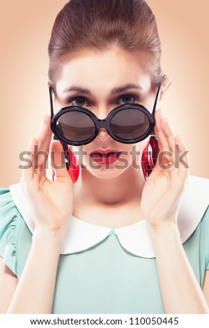 Beautiful young woman with glamour red lips wearing round plastic-rimmed sunglasses and fancy plastic earrings, she's surprised and looking over the top of her glasses. Colored background, pinup style - stock photo