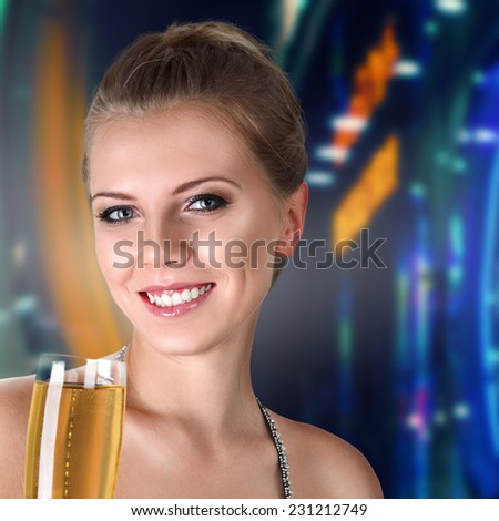 Beautiful young woman with glass of champagne in hands against illuminated background - stock photo