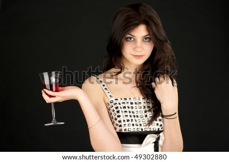 Beautiful young woman with glass of red wine over black background - stock photo