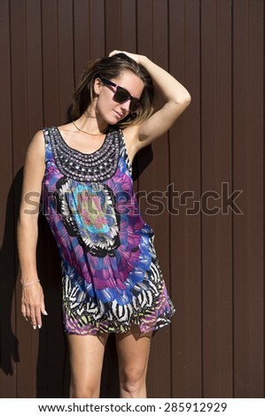 Beautiful young woman with glasses standing in front of a brown fence, fashion style bright summer dress. - stock photo