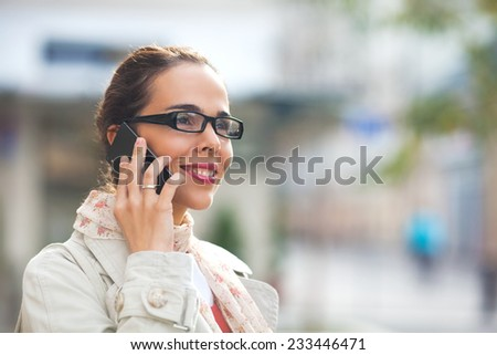 Beautiful young woman with glasses talking on the smart phone on the street